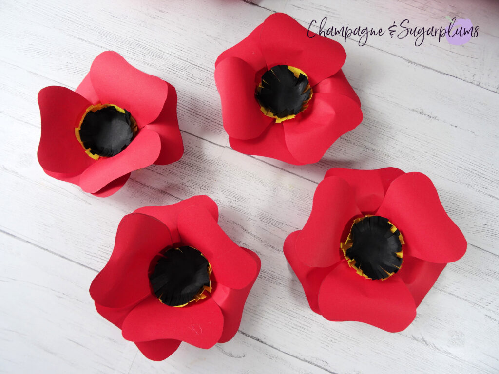 Four completed medium sized red paper flowers by Champagne and Sugarplums