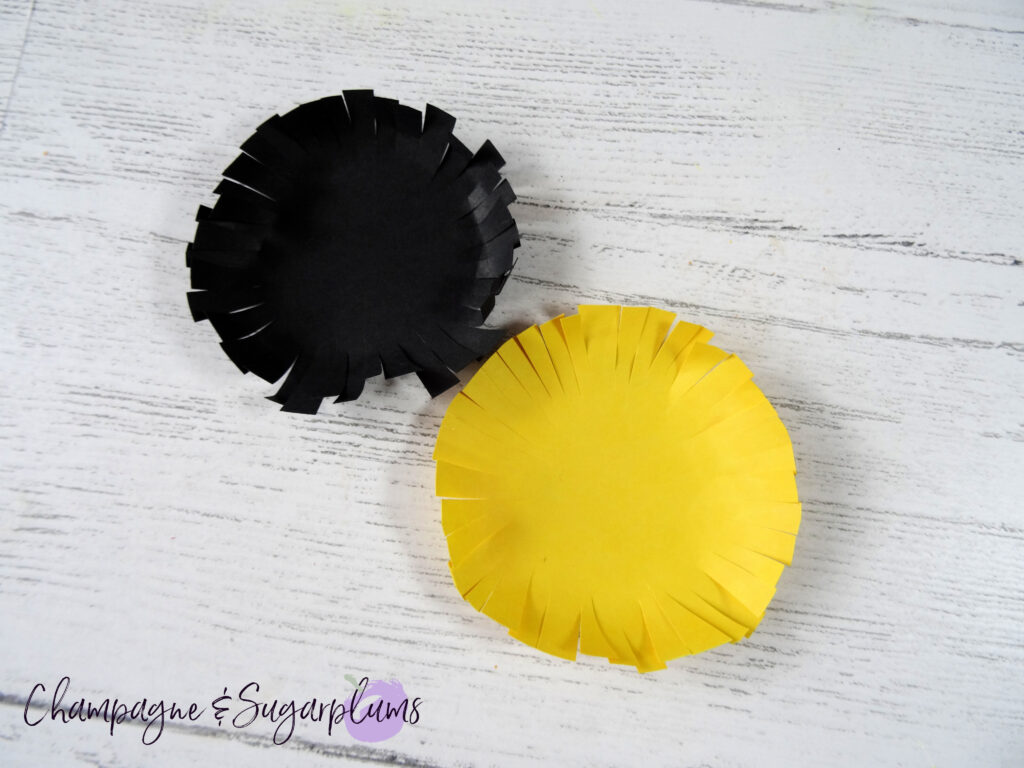 One black and one yellow fringed circle side by side on a white background by Champagne and Sugarplums