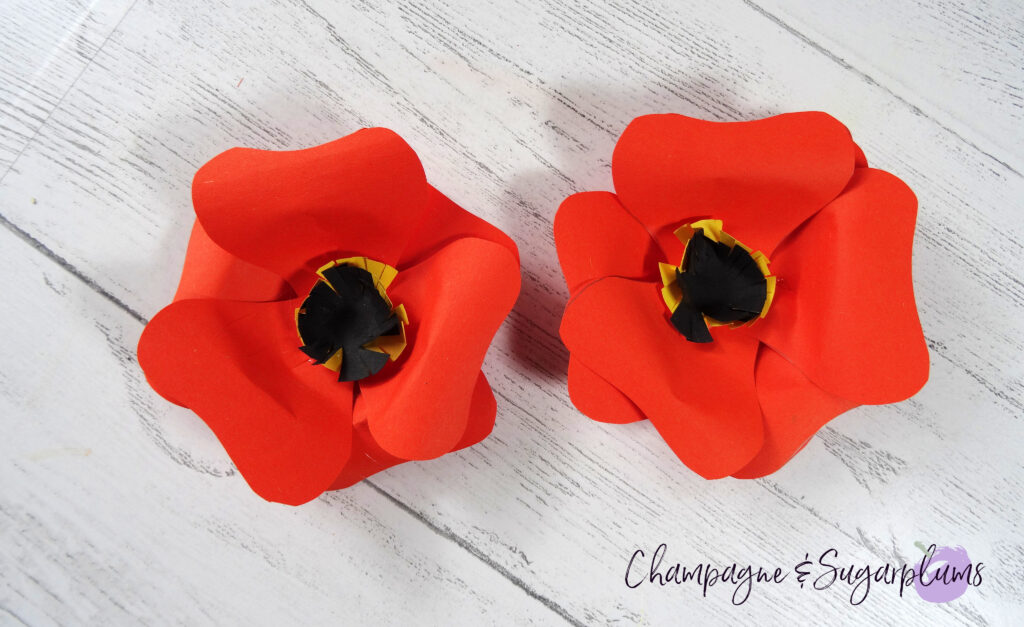 Two completed small sized orange paper flowers by Champagne and Sugarplums