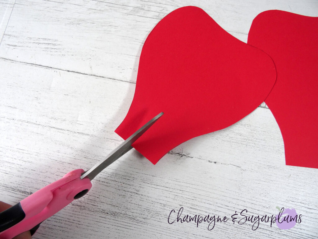 Cutting slits into the bottom of red paper flower petals by Champagne and Sugarplums