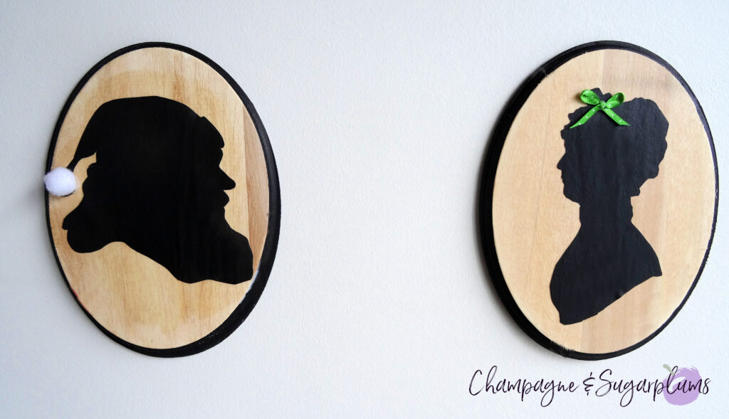 Santa and Mrs. Claus silhouettes on two wooden oval plaques, hanging on a white wall by Champagne and Sugarplums