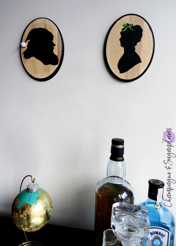 Santa and Mrs. Claus silhouettes on two wooden oval plaques, hanging on a white wall above a bar by Champagne and Sugarplums