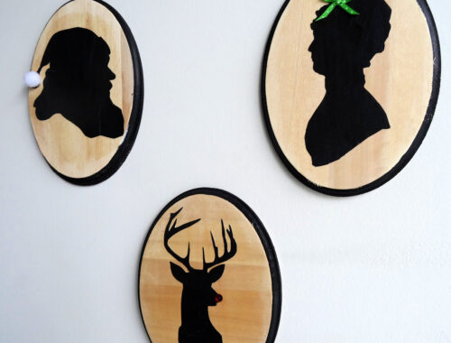 Three oval wood plaques with silhouettes of Santa, Mrs. Claus and Rudolf on a white background by Champagne and Sugarplums