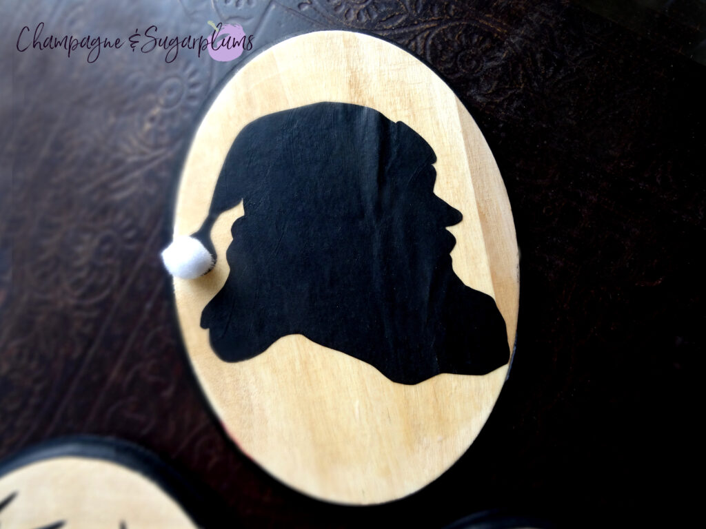 Santa silhouette on a wood board on a dark background by Champagne and Sugarplums