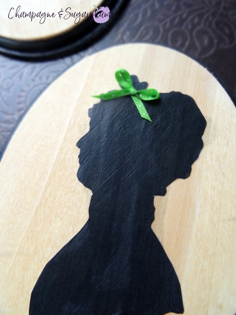 Adding a green bow to a Mrs. Claus silhouette on a wood board by Champagne and Sugarplums