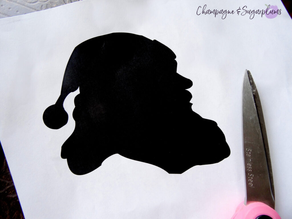 Cutting out a black Santa silhouette from a white piece of paper by Champagne and Sugarplums