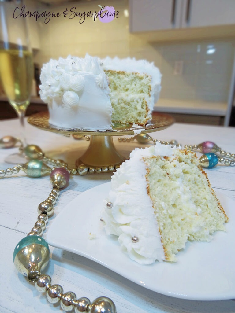 Champagne Cake sliced on white pate with a decorative stand  with champagne flutes and garland by Champagne and Sugarplums