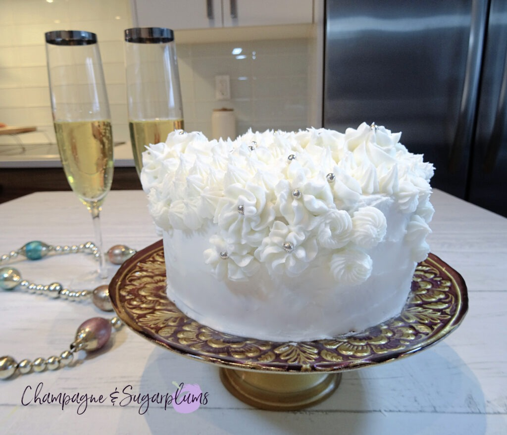 Champagne Cake sliced on a decorative stand with champagne flutes and garland by Champagne and Sugarplums