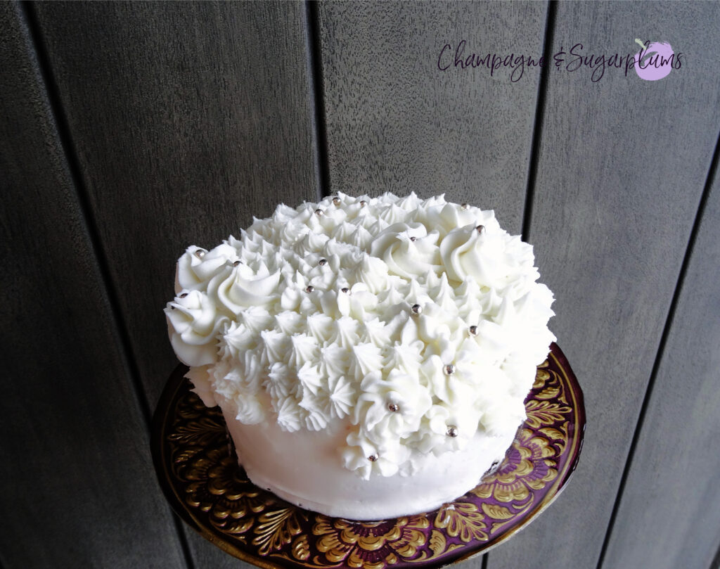 Champagne Cake sliced on a decorative stand in front of a wood background by Champagne and Sugarplums
