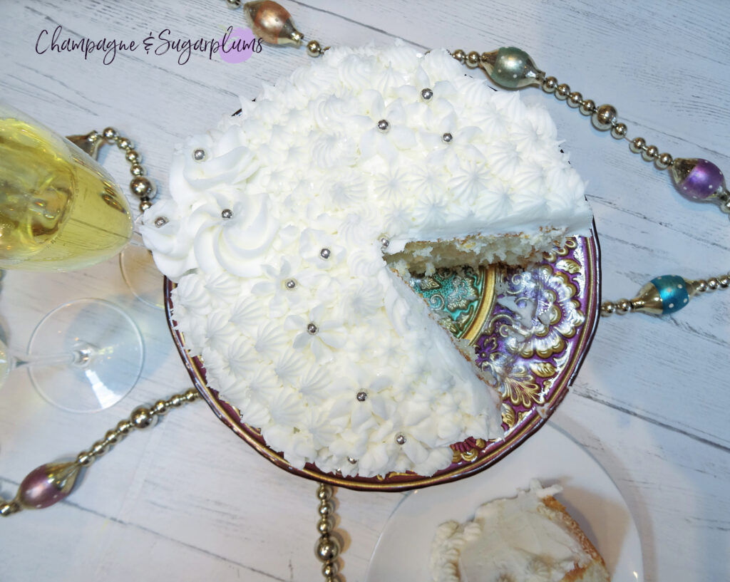 Champagne Cake on a decorative stand  with champagne flutes and garland by Champagne and Sugarplums