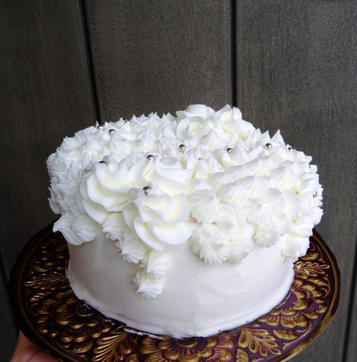 Champagne cake on a cake stand by Champagne and Sugarplums