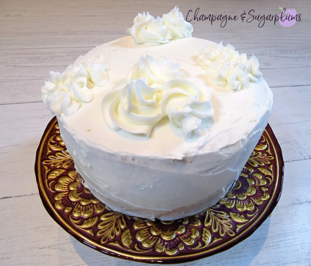 Icing a cake with white icing by Champagne and Sugarplums