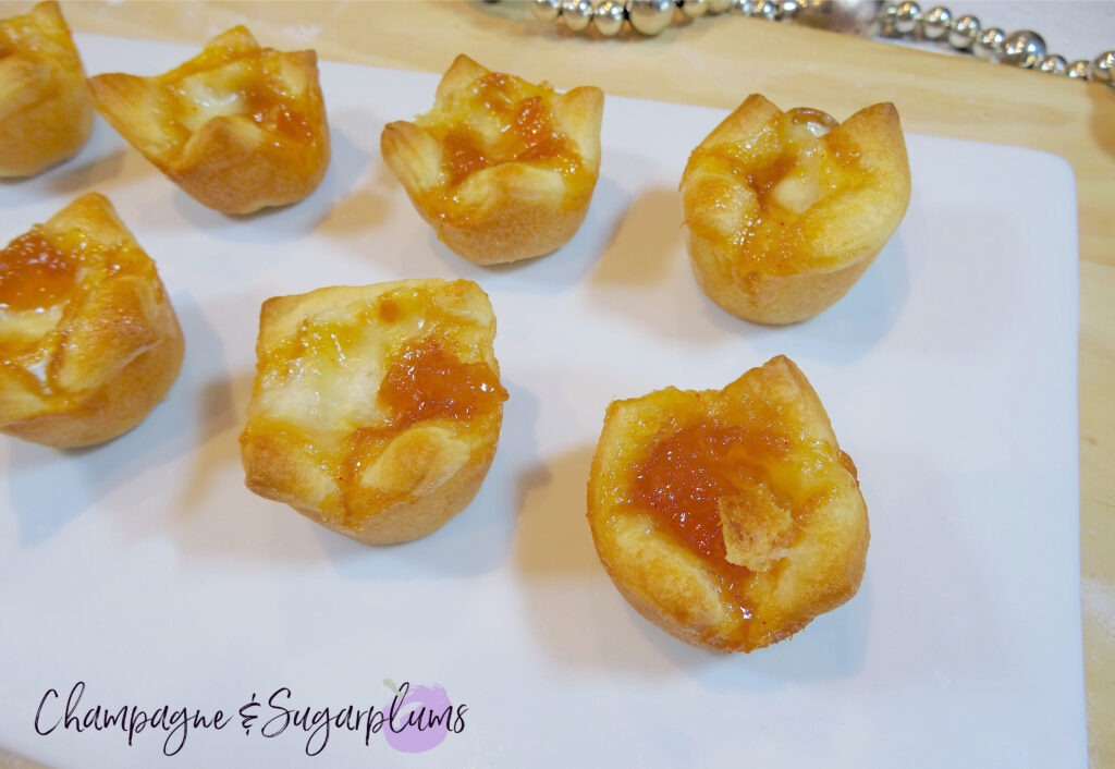 Mango Brie Bites on a white plate with glass garland by Champagne and Sugarplums