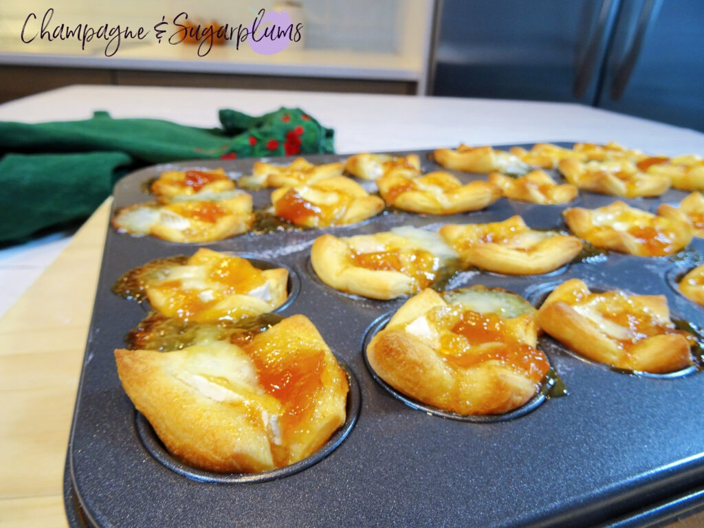 Mini muffin tin filled with baked dough squares with Brie and mango chutney on a wood board by Champagne and Sugarplums