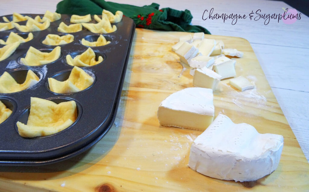 Brie cut into small pieces beside a mini muffin tin filled with dough squares on a wood board by Champagne and Sugarplums