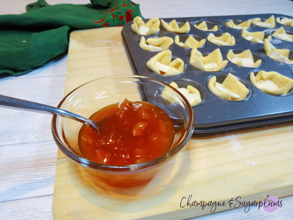 A bowl of mango chutney beside a mini muffin tin filled with dough squares with Brie pieces on a wood board by Champagne and Sugarplums