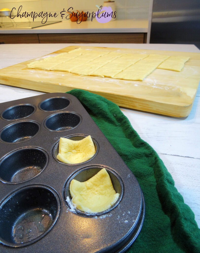 Dough spread out on a wood board with dough squares in a mini muffin tin by Champagne and Sugarplums