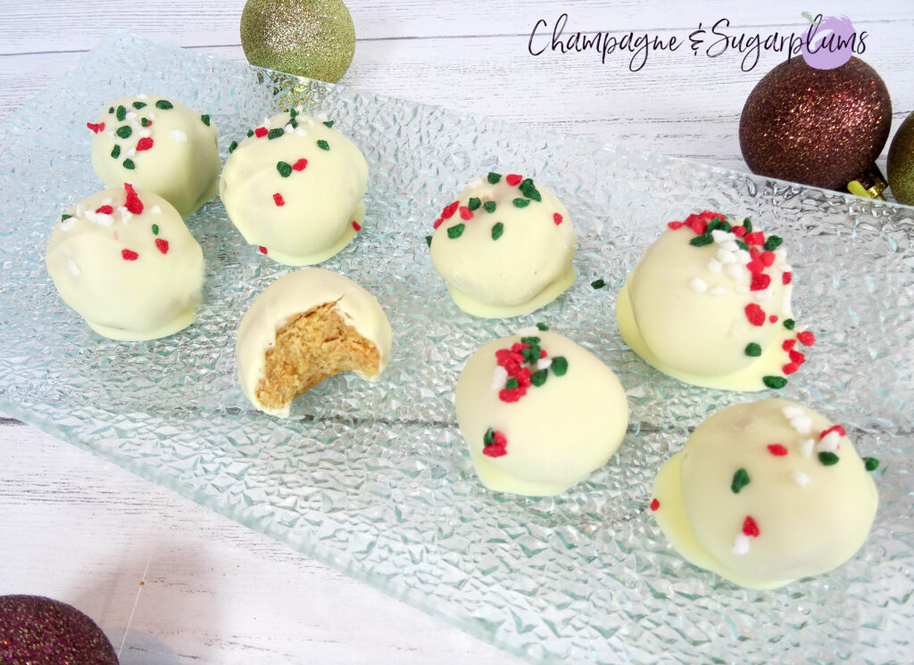 Natural Peanut Butter Snowballs, one with a bite in it, on a glass plate surrounded by ornaments on a white background by Champagne and Sugarplums