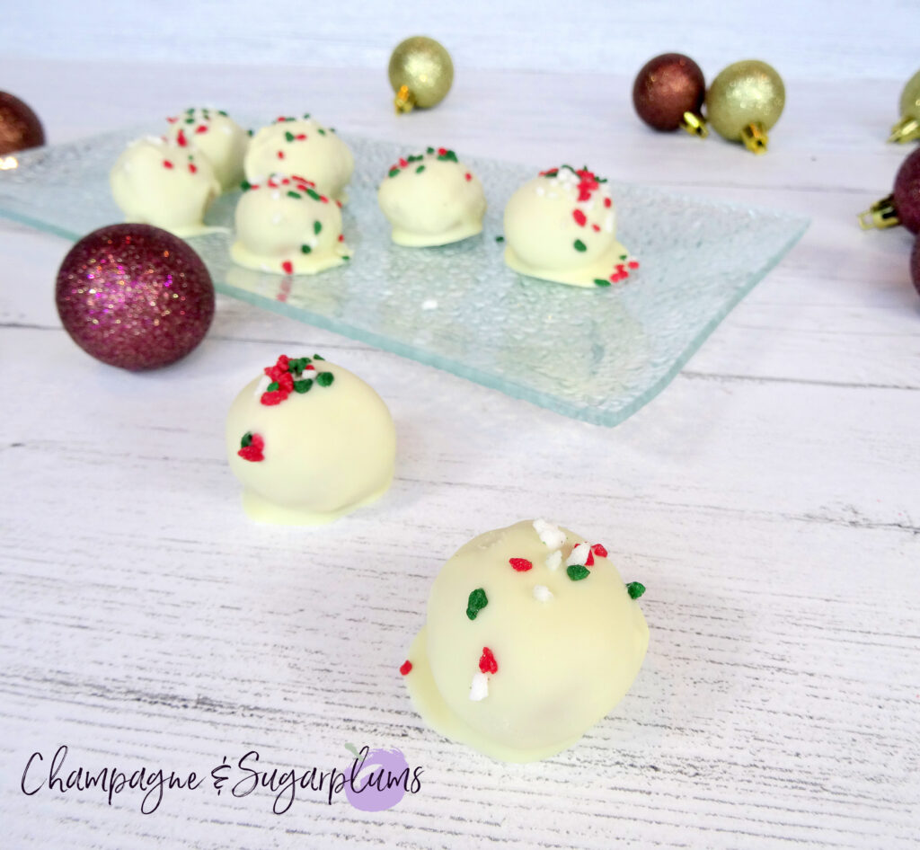 Natural Peanut Butter Snowballs on a glass plate surrounded by ornaments on a white background by Champagne and Sugarplums