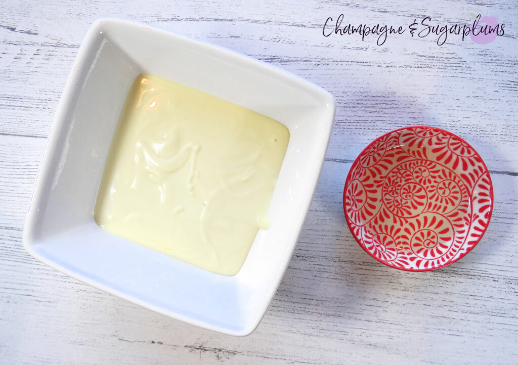 A square bowl with melted white chocolate and a red pinch bowl with oil on white background by Champagne and Sugarplums