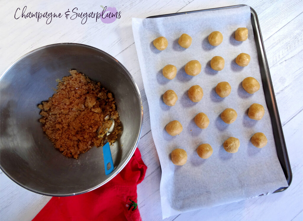 Snowball treats on a baking tray beside a metal mixing bowl of dough by Champagne and Sugarplums