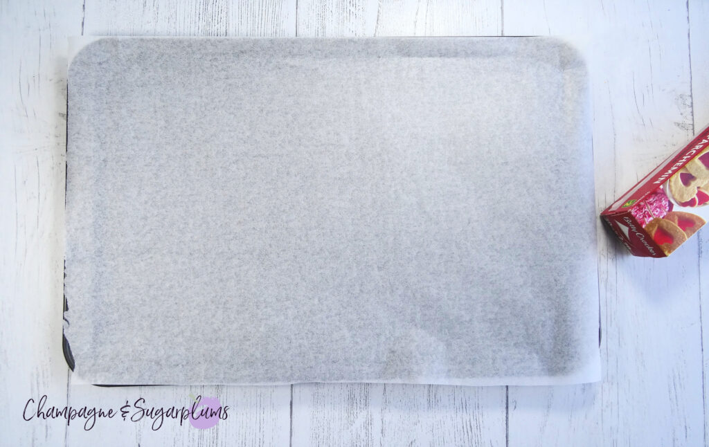 A baking tray lined with parchment paper on a white background by Champagne and Sugarplums
