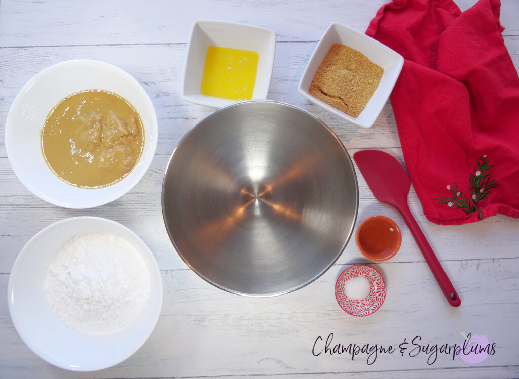 Ingredients to make snowball treats in a metal mixing bowl on a white background by Champagne and Sugarplums