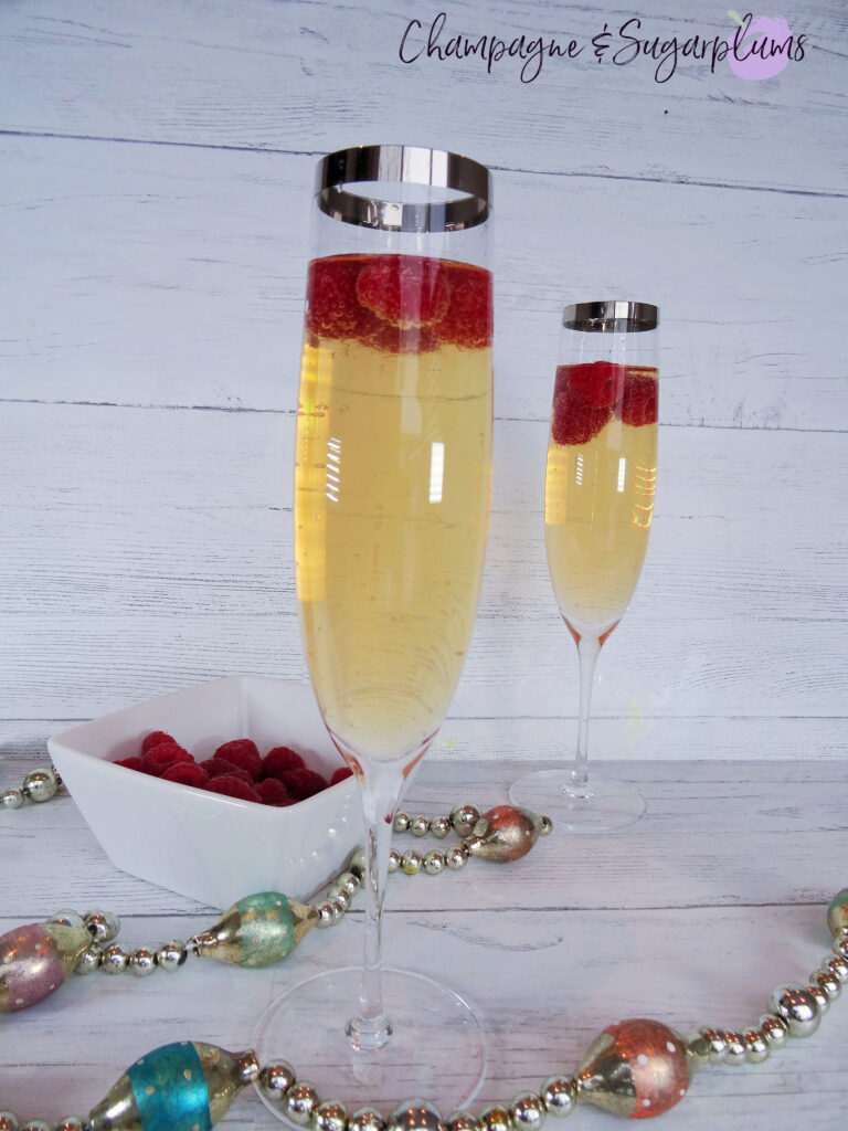 Cocktail with raspberries in a champagne flute on a white background by Champagne and Sugarplums
