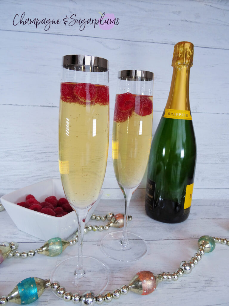 Drinks with raspberries in a champagne flute, beside a bottle on a white background by Champagne and Sugarplums