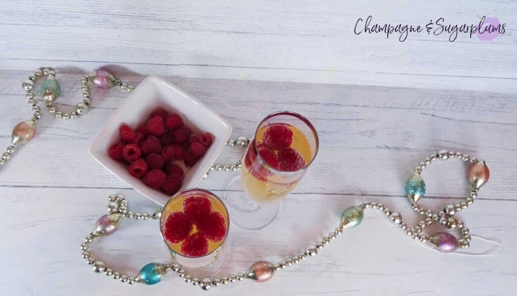 Champagne Cocktail with raspberries in a champagne flute on a white background by Champagne and Sugarplums