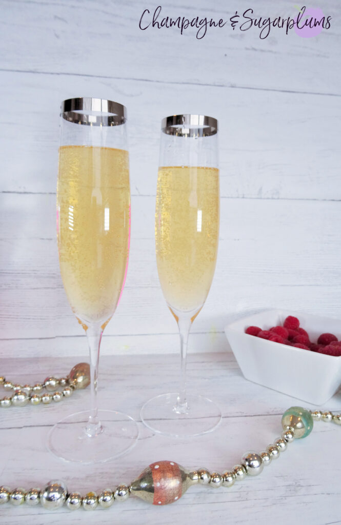 Adding champagne on top of Pink Whitney Vodka to champagne flutes by Champagne and Sugarplums