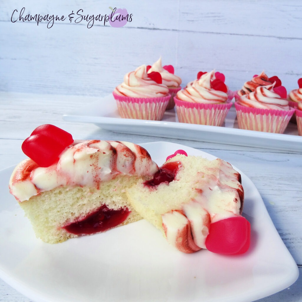 A cupcake sliced in half to reveal cherry center on a white background  by Champagne and Sugarplums