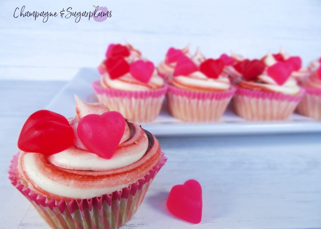 A Cherry Cupcake on a white background with a dozen more cupcakes on a white plate in the background by Champagne and Sugarplums