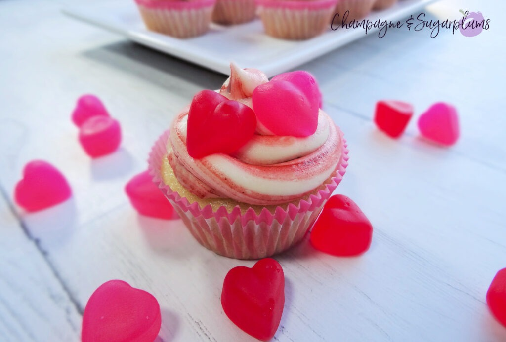 A Cupcake on a white background surrounded by red and pink candy hearts by Champagne and Sugarplums
