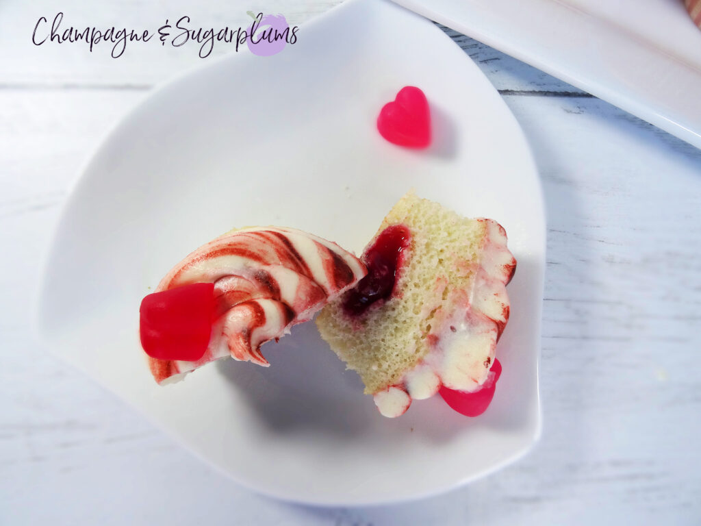 A Cherry Cupcake sliced in half to reveal cherry center on a white background  by Champagne and Sugarplums