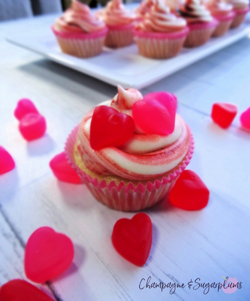 A Cherry Cupcake on a white background surrounded by red and pink candy hearts by Champagne and Sugarplums
