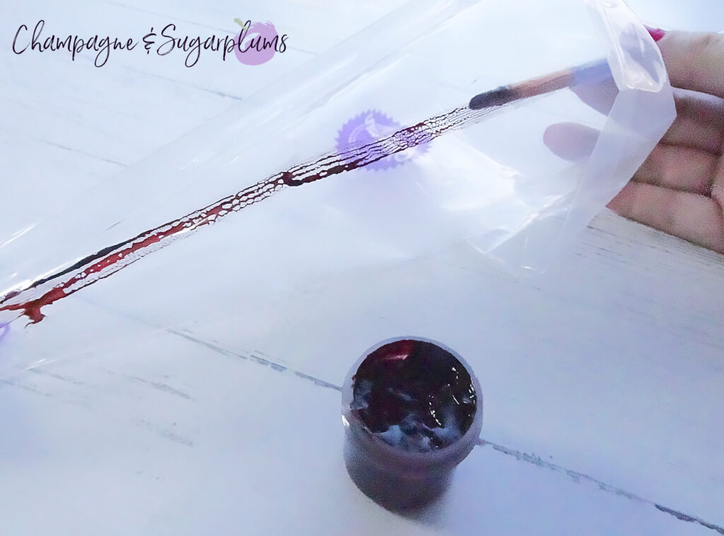 Painting pink colouring in stripes into a clear icing bag by Champagne and Sugarplums