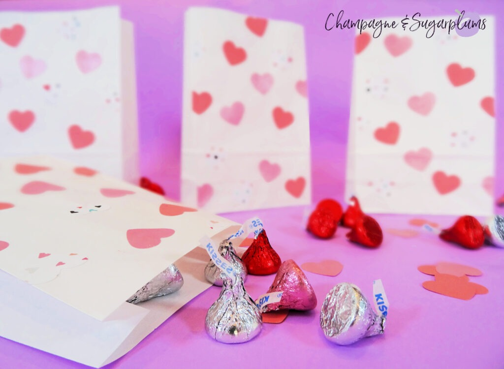 Valentine bags with pink hearts on purple background surrounded by chocolates and paper hearts by Champagne and Sugarplums