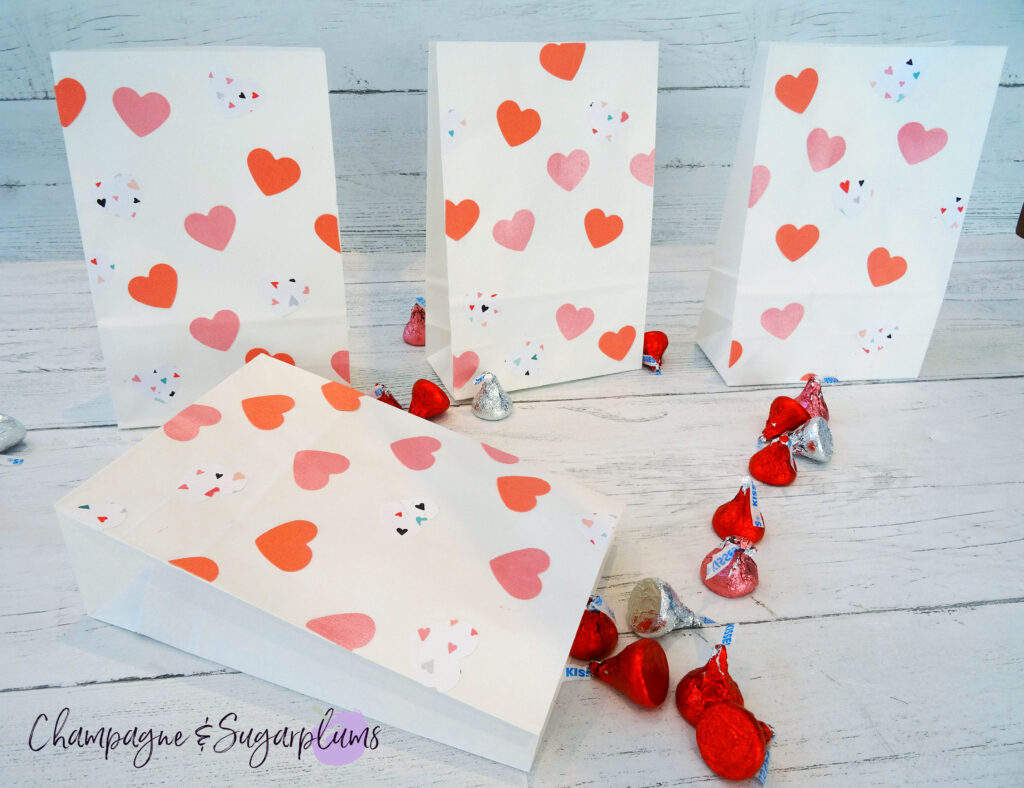Valentine Treat Bags with pink hearts on white background surrounded by chocolates by Champagne and Sugarplums
