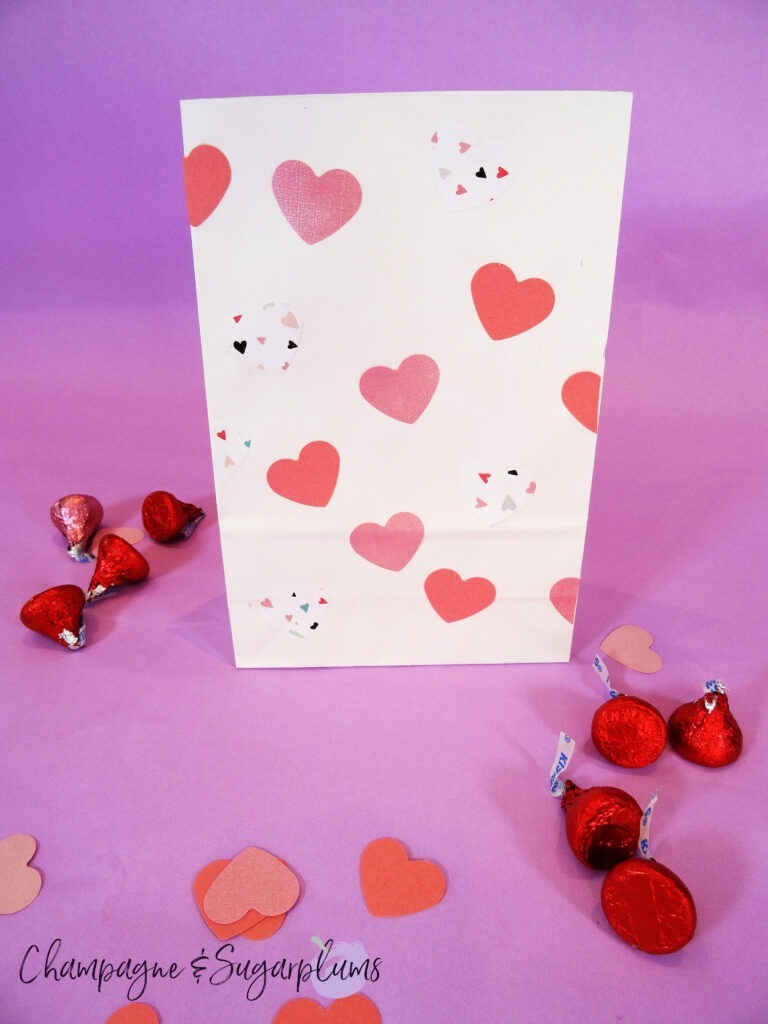 Valentine Treat Bags with pink hearts on purple background surrounded by chocolates and paper hearts by Champagne and Sugarplums