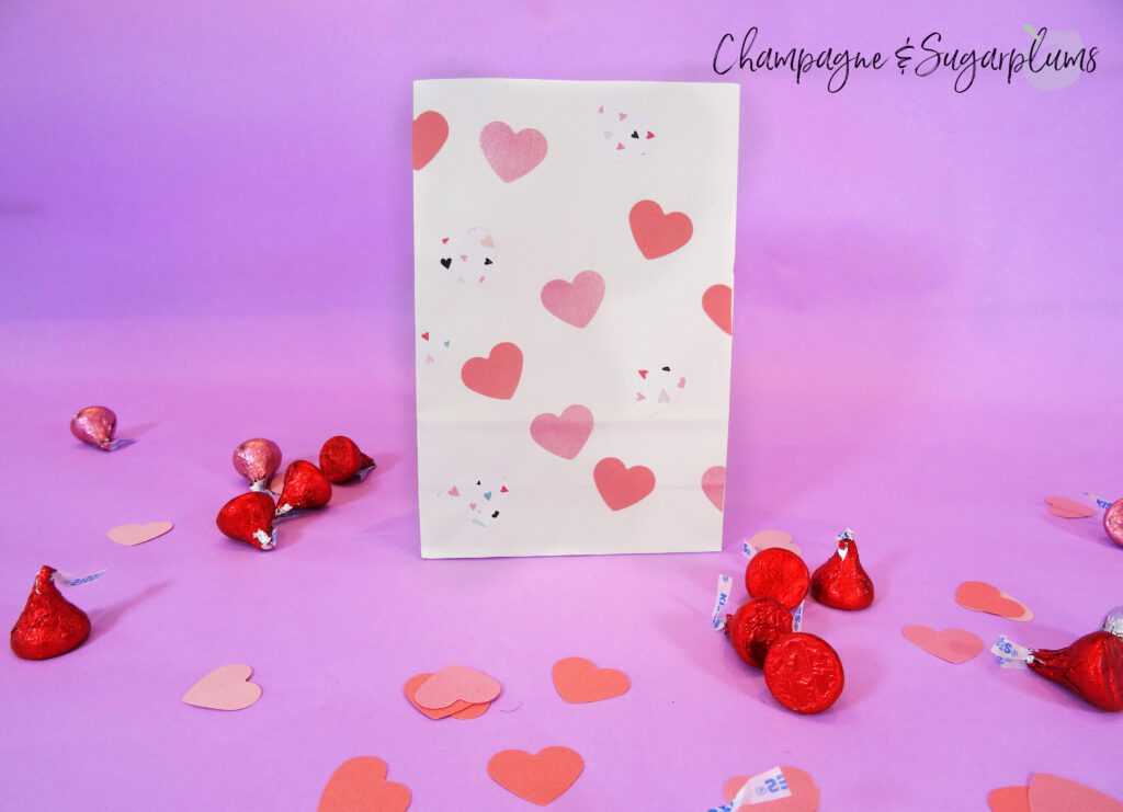 Valentine bag with pink hearts on purple background surrounded by chocolates and paper hearts by Champagne and Sugarplums