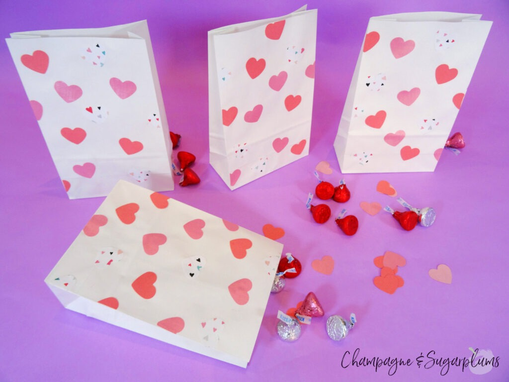 Valentine Treat Bags with pink hearts on purple background surrounded by chocolates and  by Champagne and Sugarplums