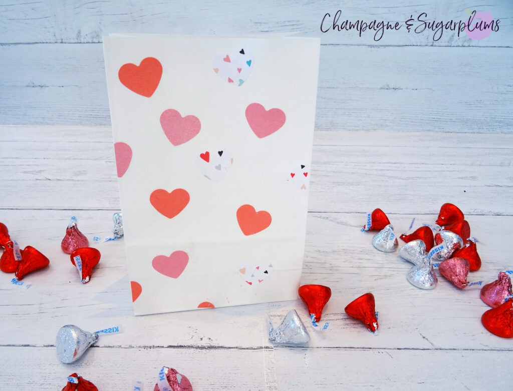 Valentine bags with pink hearts on white background surrounded by chocolates by Champagne and Sugarplums