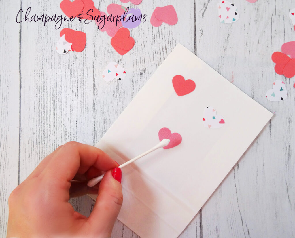 Gluing pink paper hearts onto a white paper bag on white background by Champagne and Sugarplums