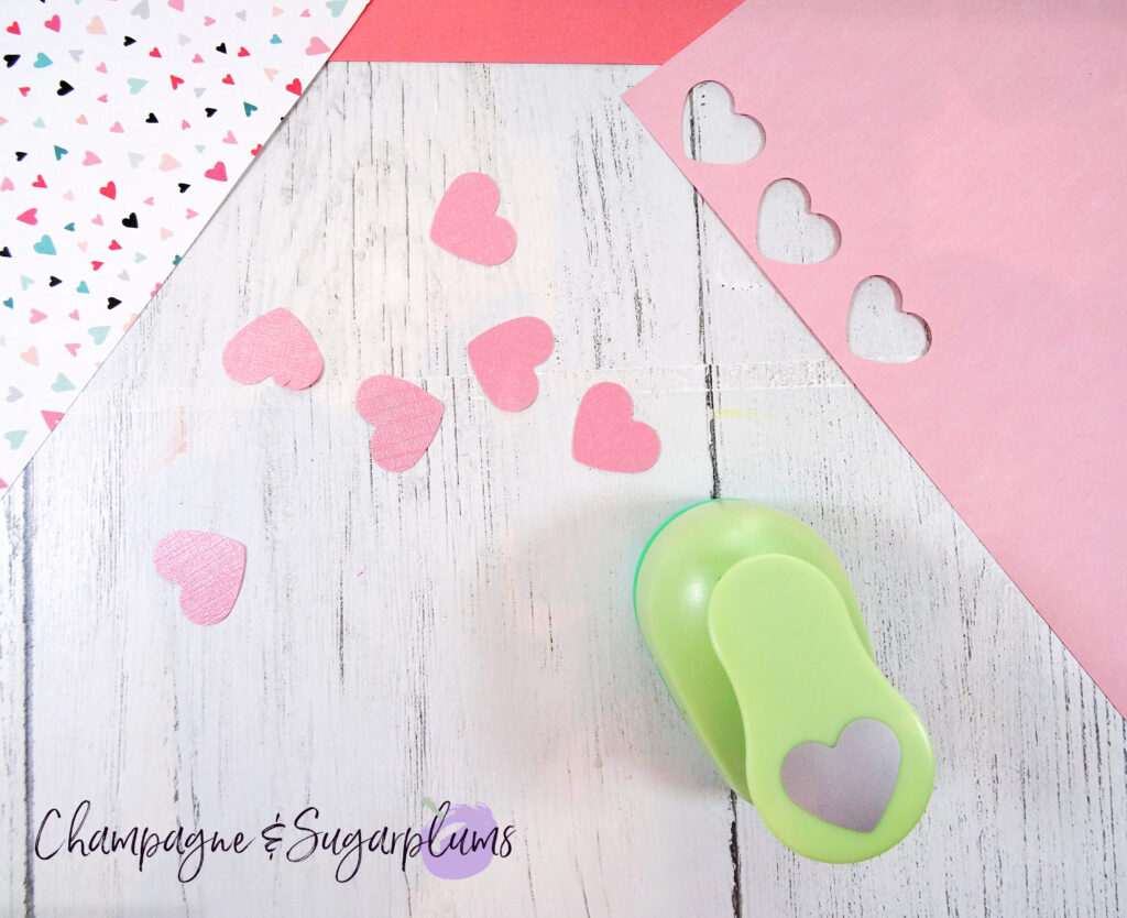Pink paper hearts and a green heart punch on a white background by Champagne and Sugarplums