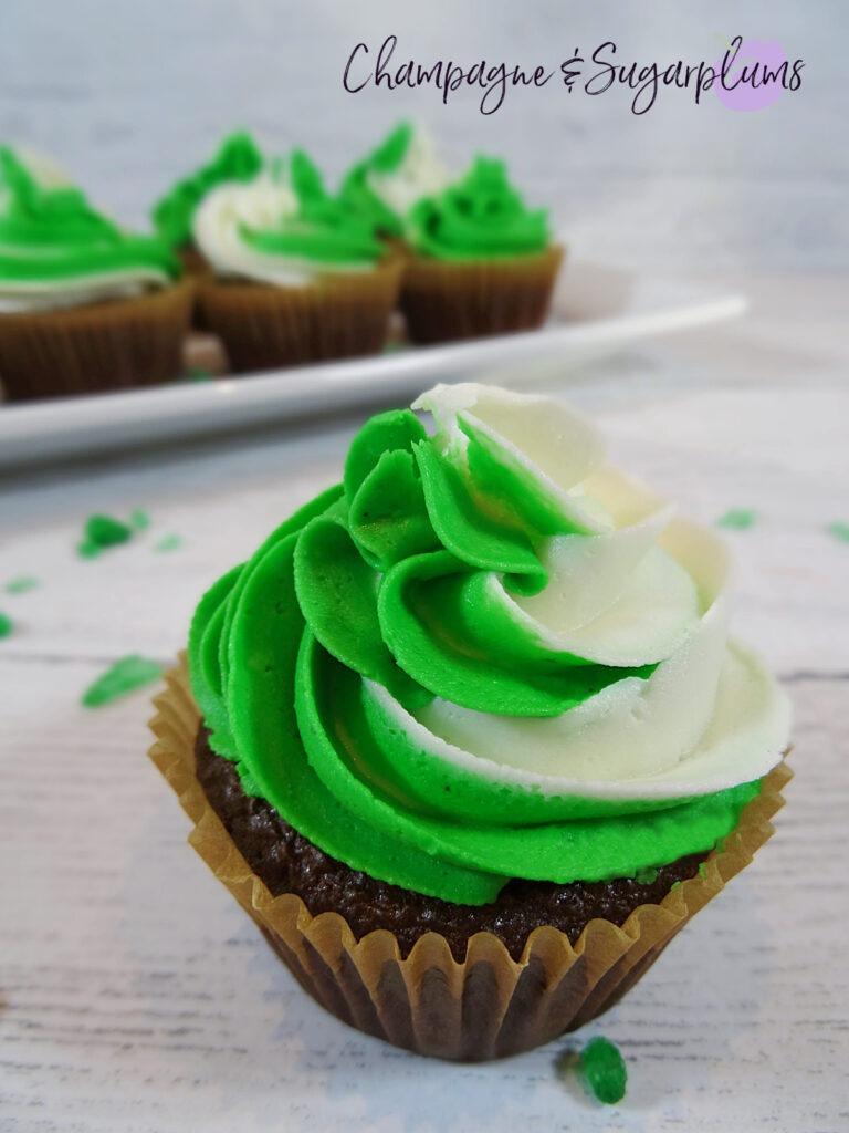 Chocolate cupcakes with peppermint frosting on a white plate with green sprinkles by Champagne and Sugarplums