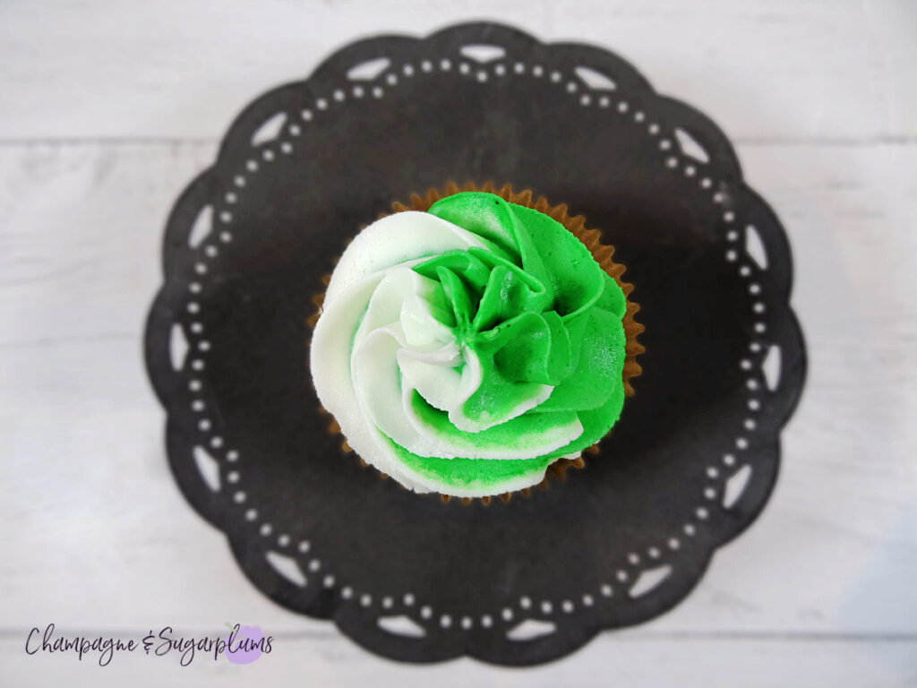 Top view of a green and white frosted cupcake sitting on a dark metal cake stand on a white background by Champagne and Sugarplums