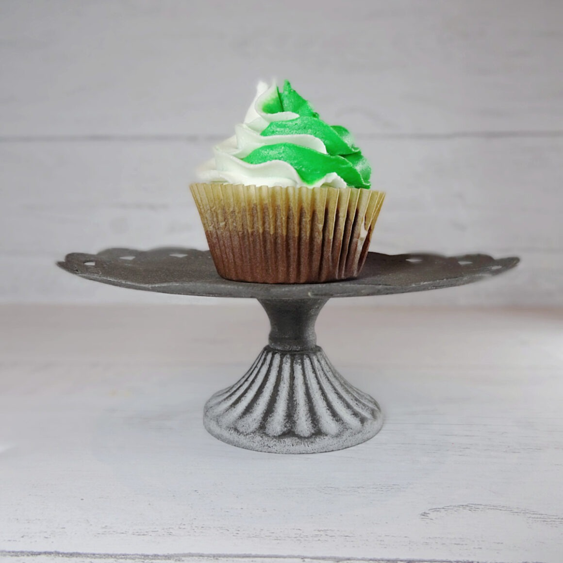 Green and white frosted chocolate cupcake on a metal stand by Champagne and Sugarplums