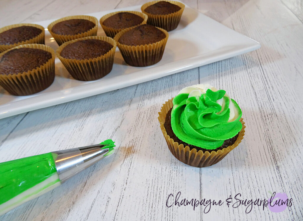 Icing chocolate cupcakes with white and green frosting on a white plate by Champagne and Sugarplums