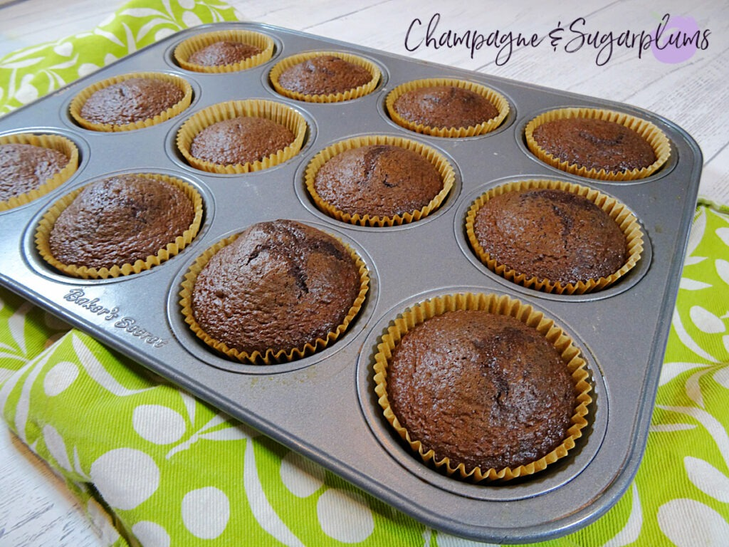 Baked chocolate cupcakes in a muffin tin beside a green tea cloth on a white background by Champagne and Sugarplums